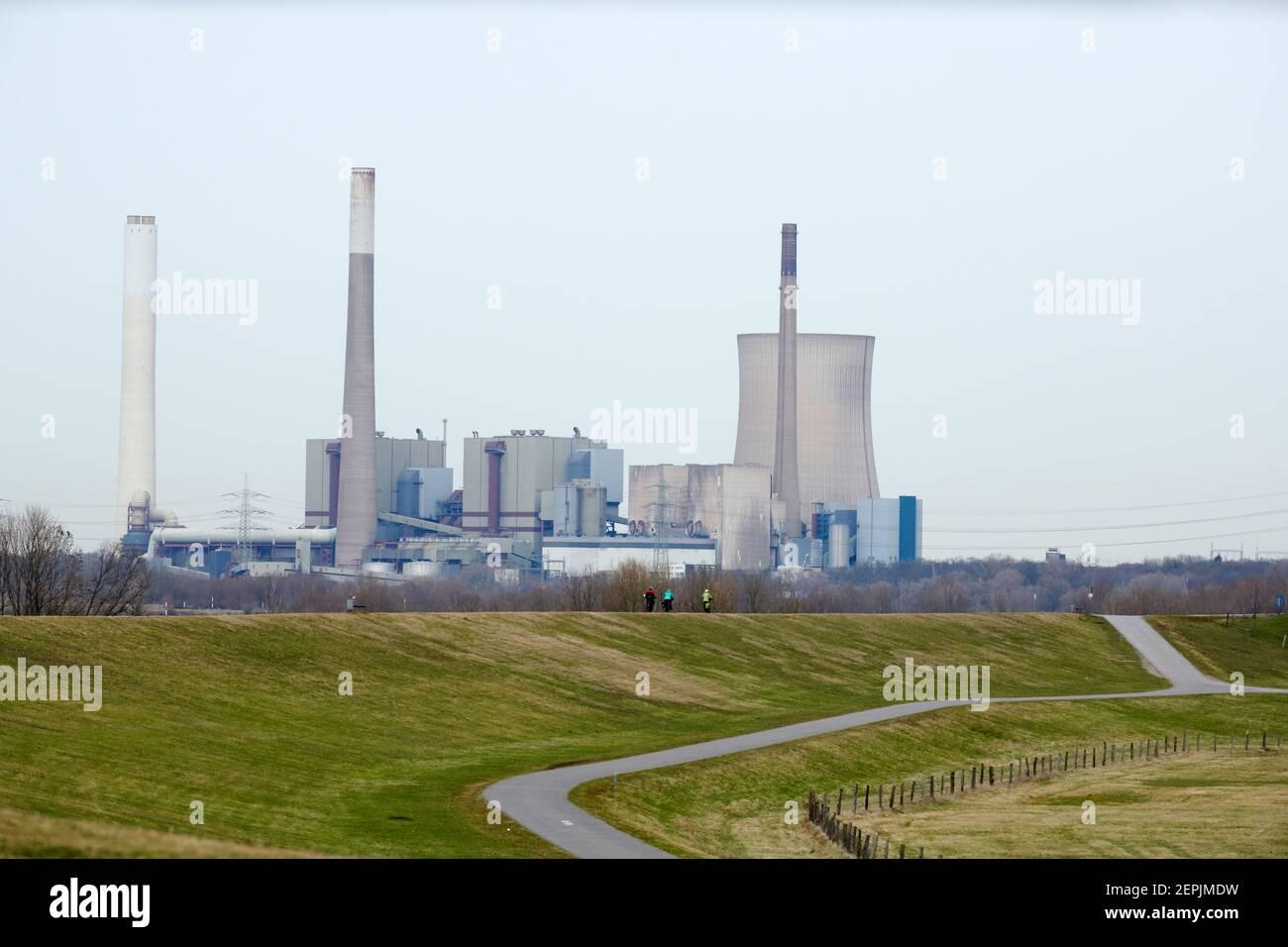 Von Duisburg Walsum aus schaut man auf das stillgelegte Kraftwerk Voerde. Im Vordergrund fahren 3 Personen Fahrrad auf dem Rheindeich. Es ist ein grau Stock Photo