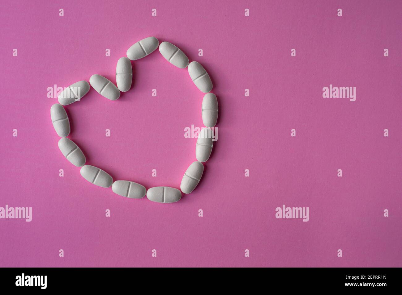 White, large pills or tablets, arranged in a heart shape to represent health on pink background Stock Photo