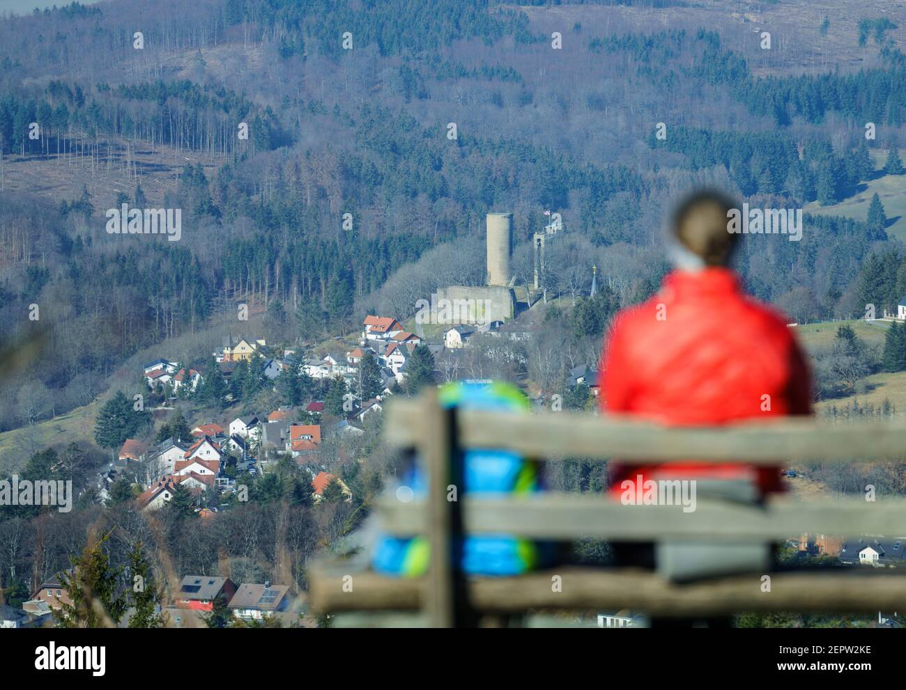 Schmitten, Germany. 28th Feb, 2021. A woman sits on a bench on the Feldberg plateau with a view of Reifenberg Castle. With temperatures around 2 degrees Celsius, many people make a trip to the local mountain in the Rhine-Main region. Credit: Andreas Arnold/dpa/Alamy Live News Stock Photo