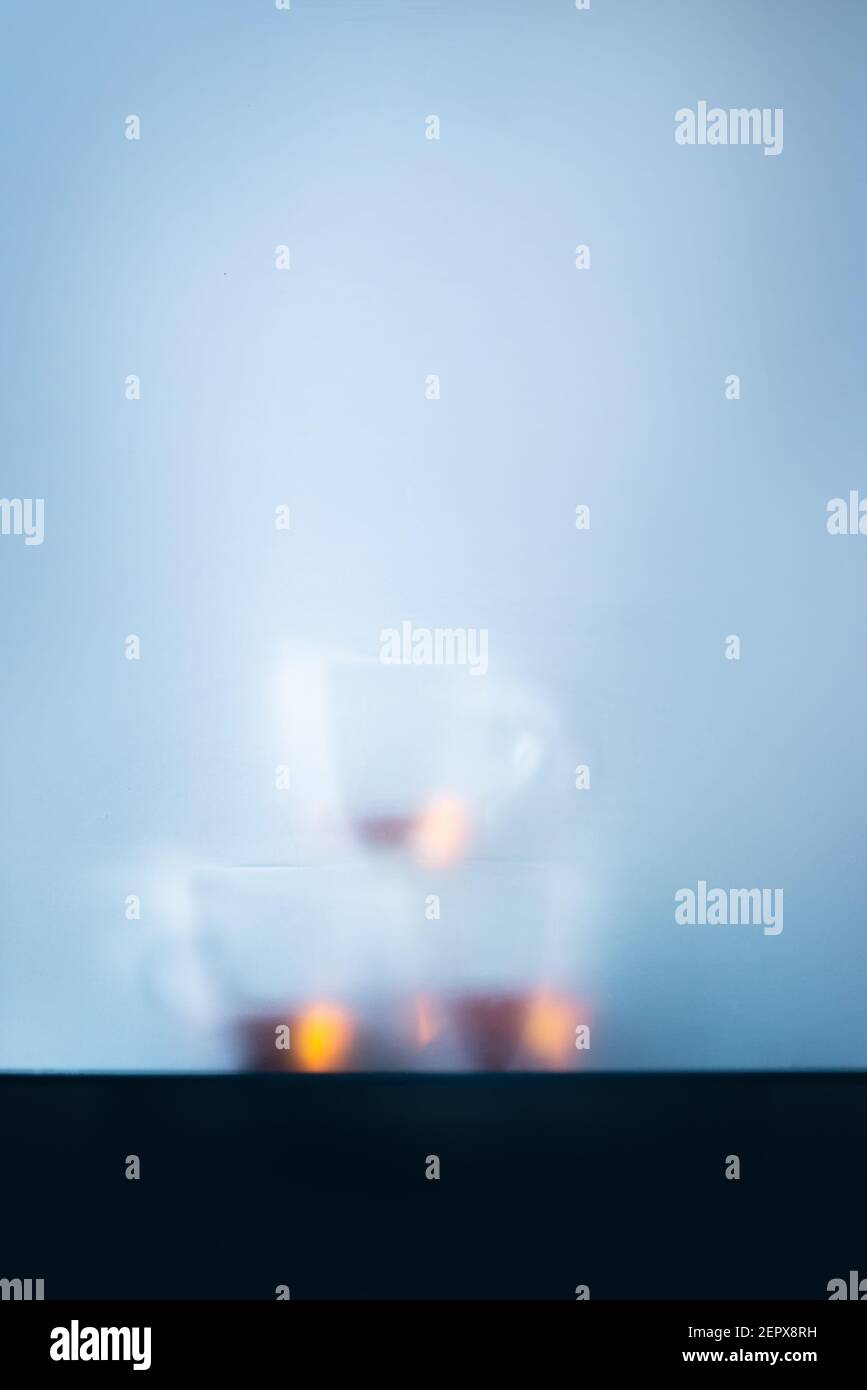 Glass teacups pyramid behind a matte glass, cold morning atmosphere Stock Photo