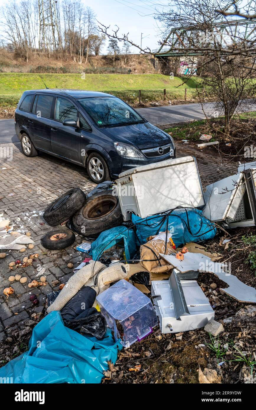 Illegal waste disposal in a car park, at a wooded area, tyres, furniture, refrigerators, household waste, oil cans, Oberhausen NRW, Germany, Stock Photo