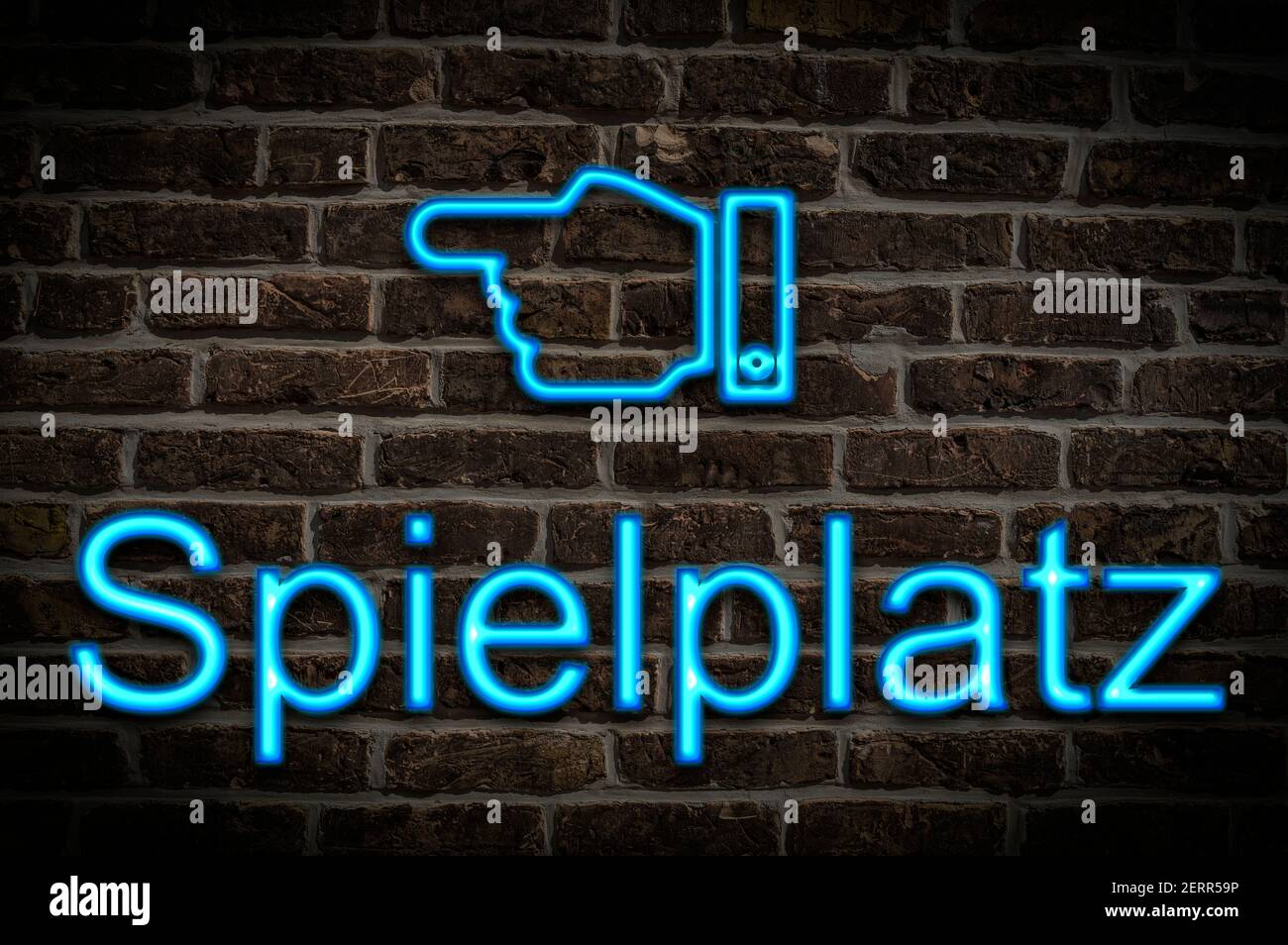 Detail photo of a neon sign on a wall with the inscription Spielplatz (Playground) Stock Photo