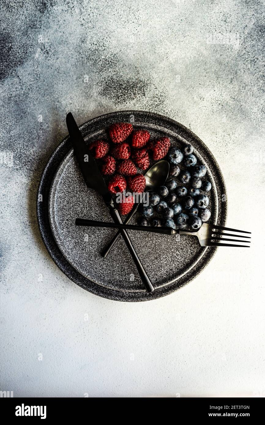 Blueberries and raspberries arranged on a plate to convey intermittent fasting concept Stock Photo