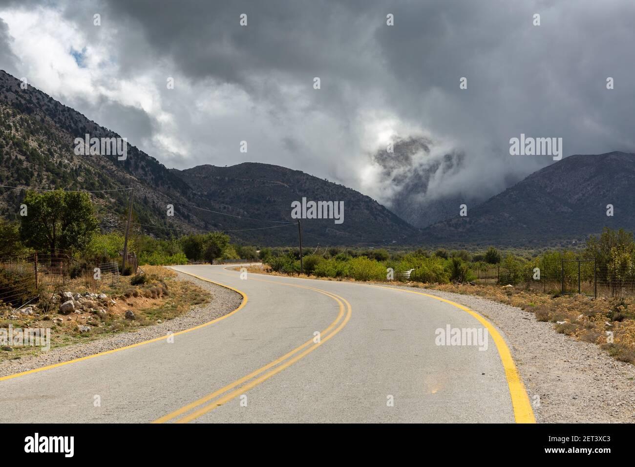 Dramatic clouds over a road and mountainous landscape near the Samaria Gorge trailhead, Crete, Greece Stock Photo