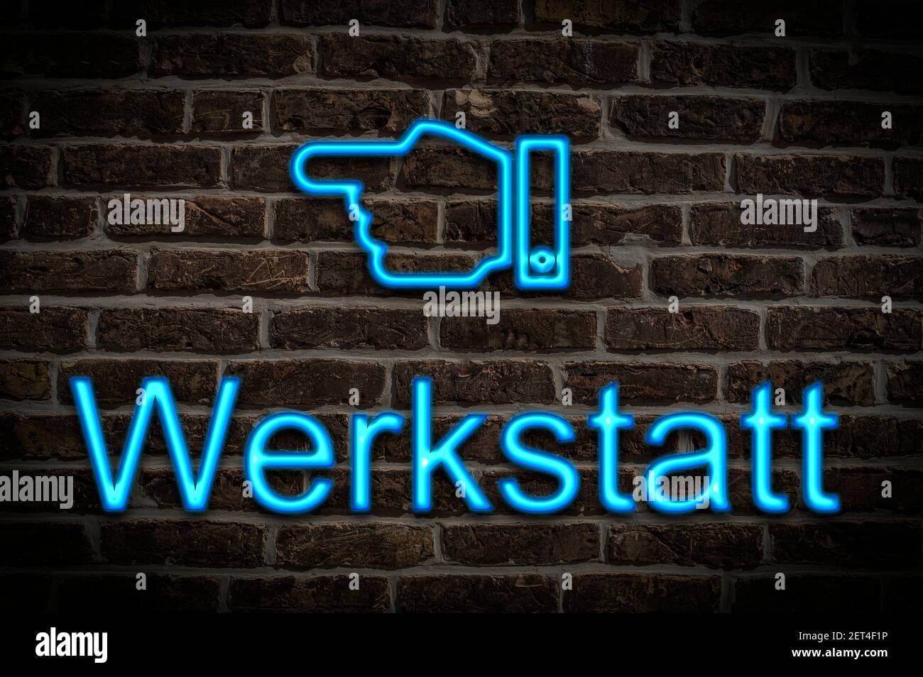 Detail photo of a neon sign on a wall with the inscription Werkstatt (Workshop) Stock Photo