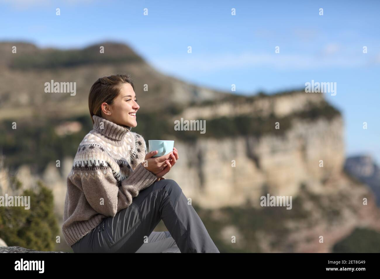Happy trekker drinking coffee looking away contemplating views sitting in the mountain in winter Stock Photo