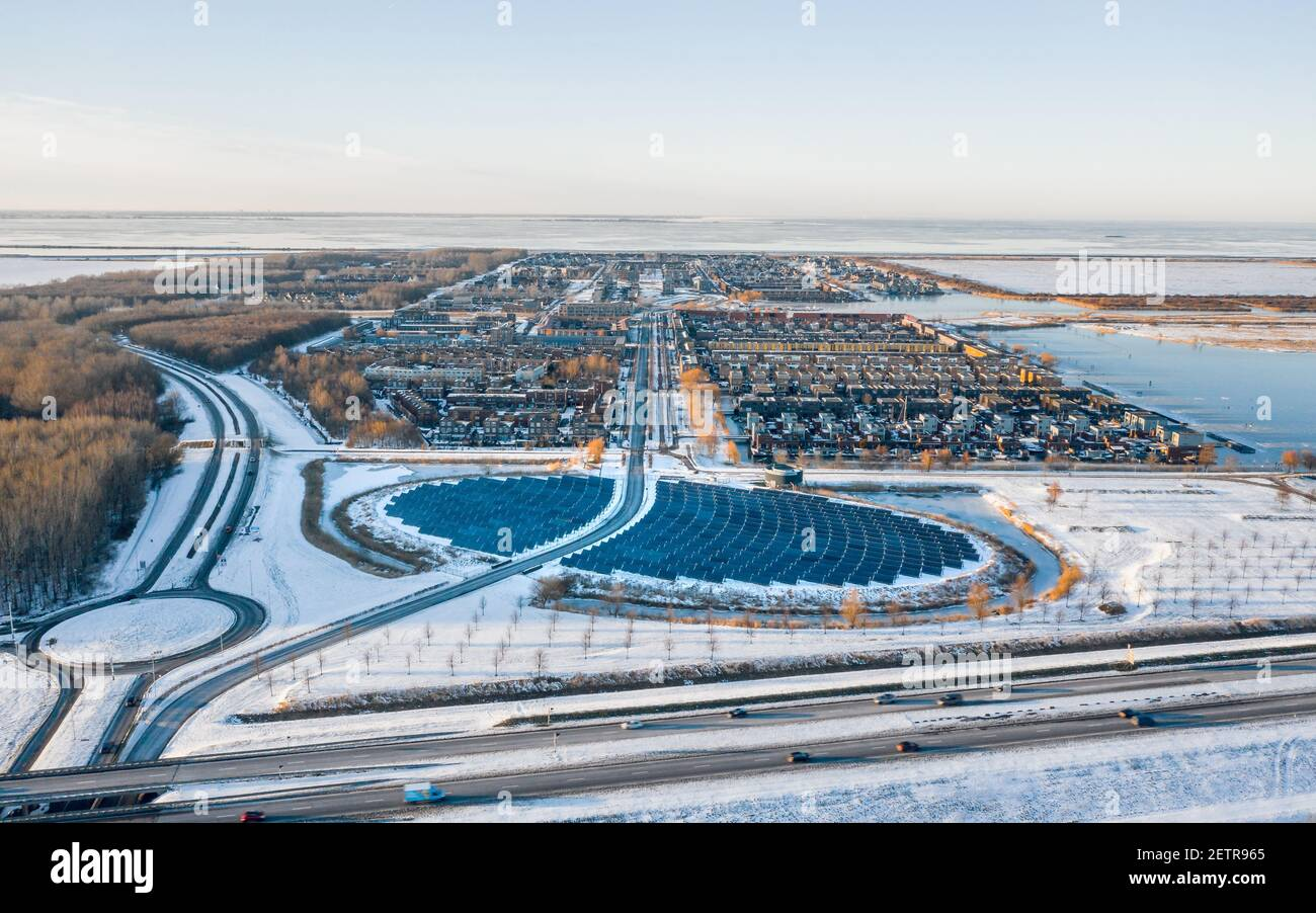 Modern sustainable neighbourhood surrounded by nature in Almere, The Netherlands, powered by solar energy. Winter landscape. Aerial shot. Stock Photo