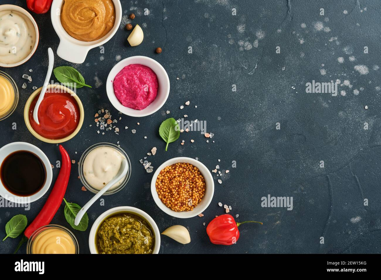 Set of sauces in bowls - ketchup, mayonnaise, mustard, soy sauce, bbq sauce, pesto, chimichurri, mustard grains on dark stone background. Top view cop Stock Photo