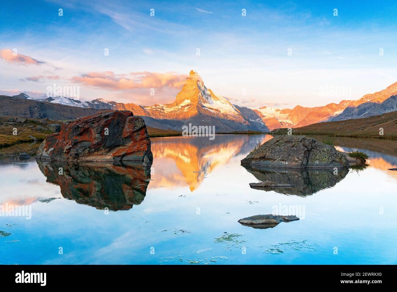 Matterhorn lit by sunrise reflected in the calm water of lake Stellisee, Zermatt, Valais Canton, Switzerland, Europe Stock Photo