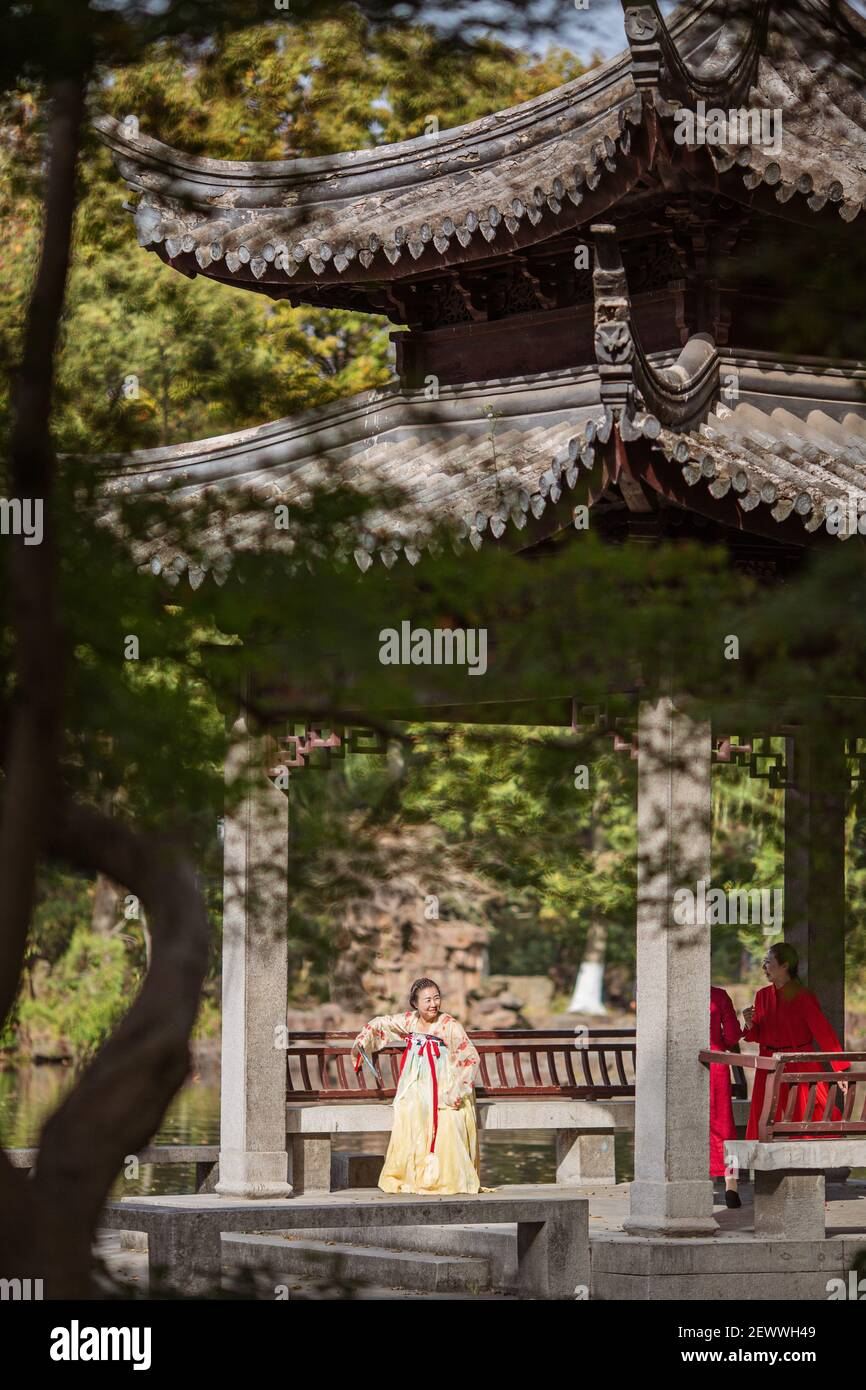 Huzhou, China, 18 November 2020: Chinese woman wearing traditional dress and holding fan in park in China. Happy Spring Festival, Chinese New Year Stock Photo