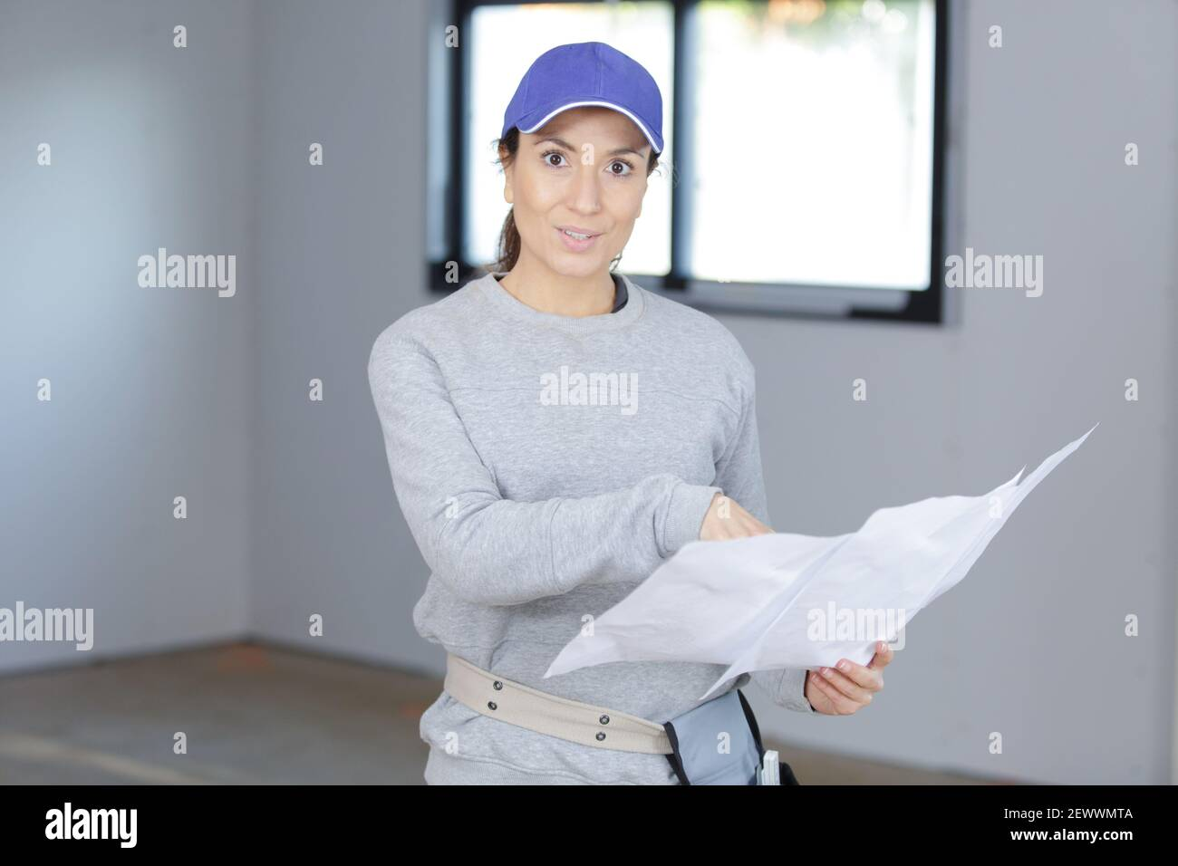 a female enginer checking plans Stock Photo