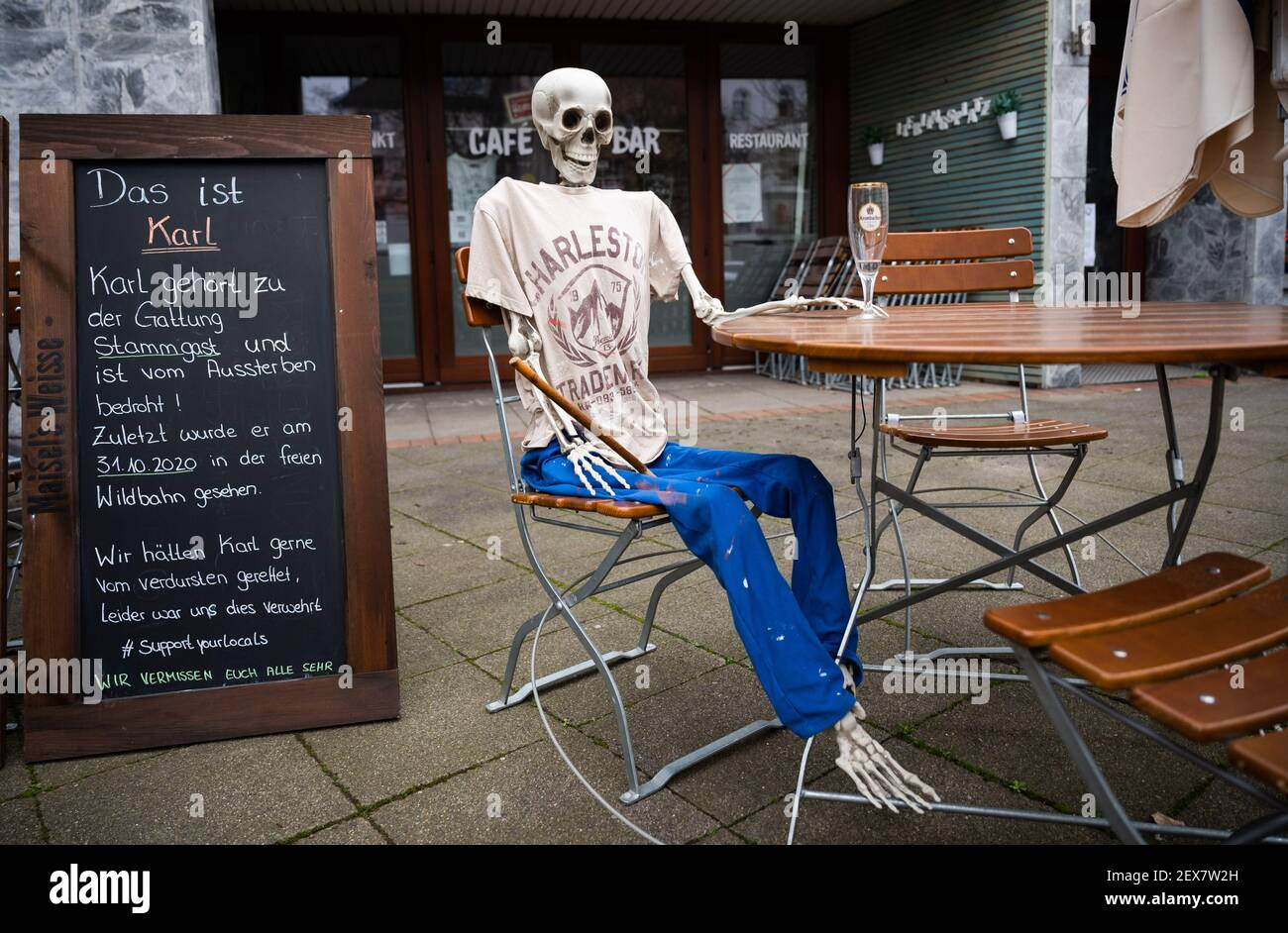 04 March 2021, Lower Saxony, Hanover: A skeleton sits with an empty beer glass outside a restaurant closed due to the Corona pandemic in Südstadt. The lockdown in Germany is extended until March 28. Photo: Julian Stratenschulte/dpa Stock Photo