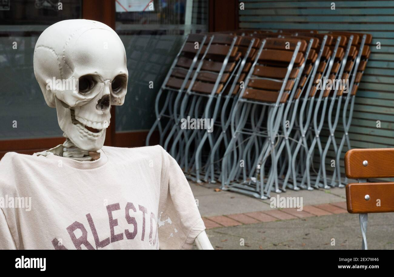 04 March 2021, Lower Saxony, Hanover: A skeleton sits outside a restaurant closed due to the Corona pandemic in Südstadt. The lockdown in Germany is extended until March 28. Photo: Julian Stratenschulte/dpa Stock Photo