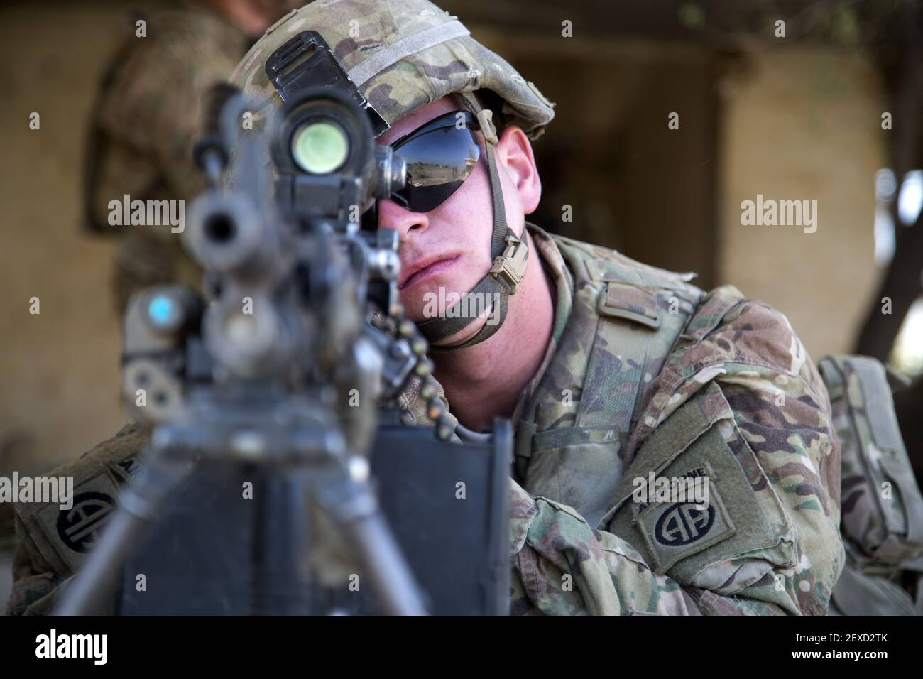 U.S. Army Pfc. Eric Krussier, a paratrooper assigned to Bravo Troop, 5th Squadron, 73rd Cavalry Regiment, 3rd Brigade, 82nd Airborne Division, looks down his sights of his weapon while he pulls security during squad level training at Camp Taji, Iraq, Aug. 3, 2015. Coalition forces routinely practice what they plan to teach Iraqi soldiers prior to each round of instruction. Training at the building partner capacity sites is an integral part of Combined Joint Task Force – Operation Inherent Resolve's multinational effort to train Iraqi security force personnel to defeat the Islamic State of  Stock Photo