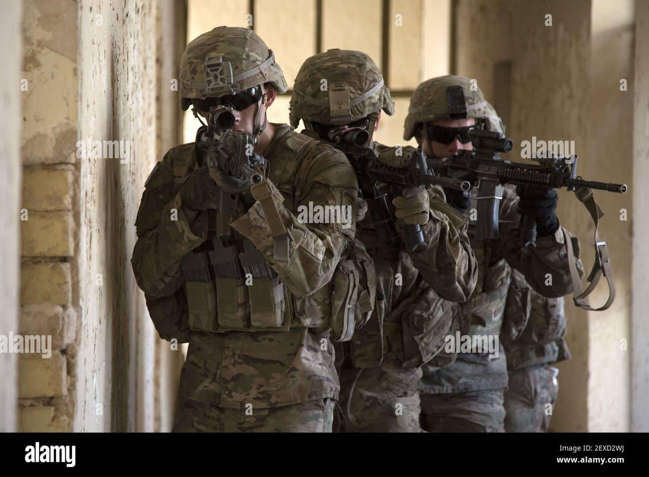 U.S. Army paratroopers assigned to Bravo Troop, 5th Squadron, 73rd Cavalry Regiment, 3rd Brigade, 82nd Airborne Division, maneuver through a hallway as part of squad level training at Camp Taji, Iraq, Aug. 3, 2015. Coalition forces routinely practice what they plan to teach Iraqi soldiers prior to each round of instruction. Training at the building partner capacity sites is an integral part of Combined Joint Task Force – Operation Inherent Resolve's multinational effort to train Iraqi security force personnel to defeat the Islamic State of Iraq and the Levant. A coalition of regional and i Stock Photo