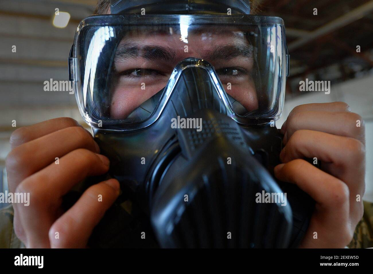 Airman 1st Class Kyle Denzine, a 20th Operations Support Squadron aircrew flight equipment specialist, checks the seal of his gas mask at Shaw Air Force Base, S.C., Oct. 23, 2015. Denzine, along with other AFE Airmen, practiced the actions they would take in the event a pilot needs to be decontaminated upon his return to base. (Photo by Senior Airman Michael Cossaboom/U.S. Air Force) *** Please Use Credit from Credit Field *** Stock Photo