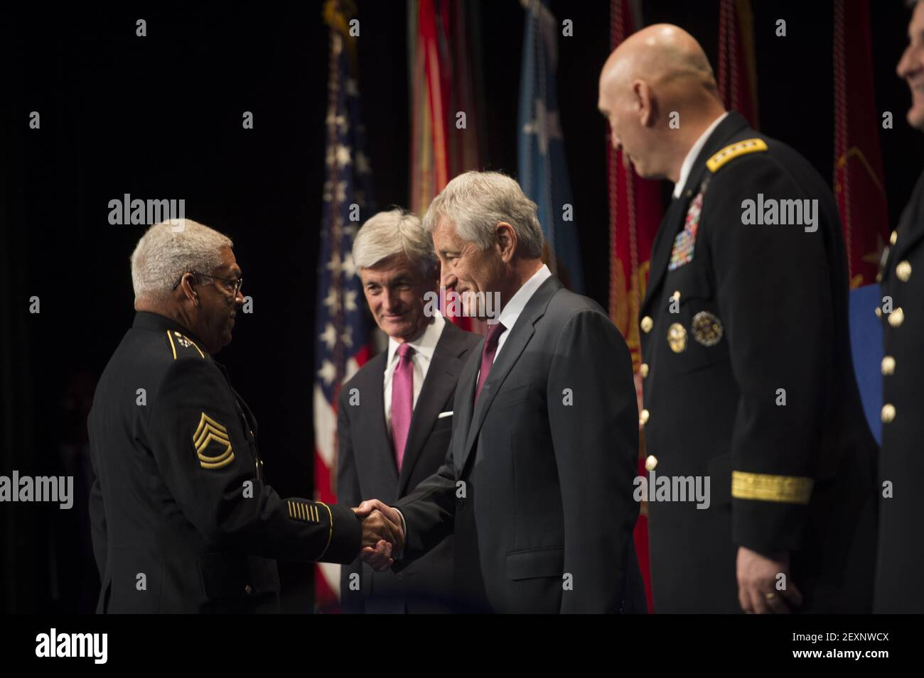 Secretary of Defense Chuck Hagel, second from right, shakes hands with retired U.S. Army Sgt. 1st Class Melvin Morris before presenting him with a Medal of Honor flag during a Hall of Heroes induction ceremony at the Pentagon in Arlington, Va., March 19, 2014. (Photo by Sgt. Aaron Hostutler, U.S. Marine Corps/DoD/Sipa USA) Stock Photo