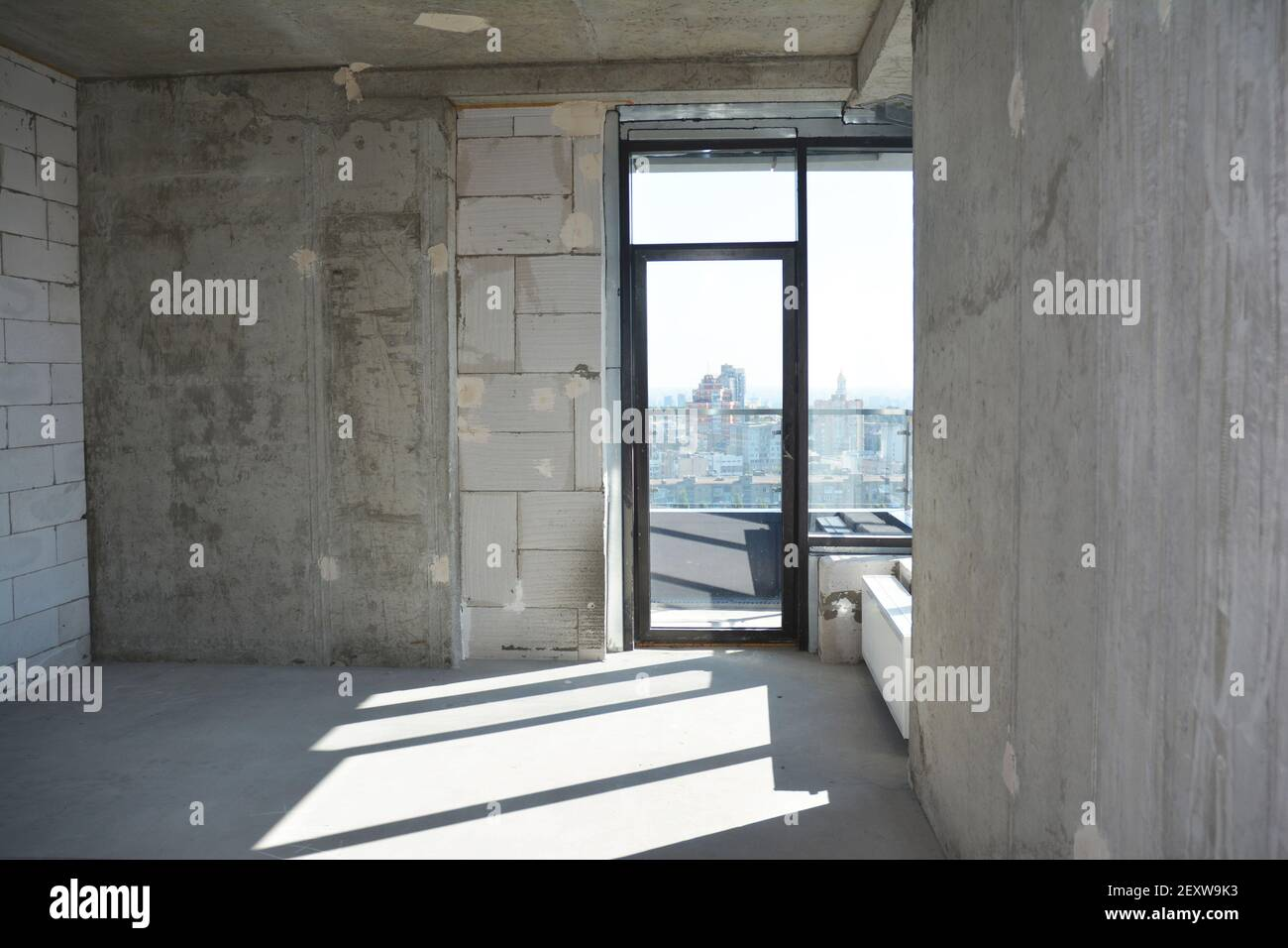 An inside view of an empty newly constructed apartment, flat without repair with a window installed in a newly built, erected residential building. Stock Photo
