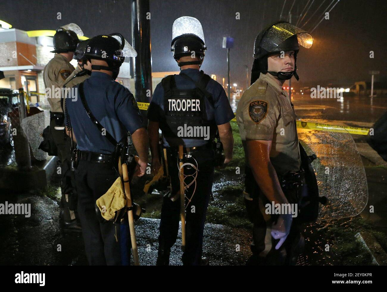 Missouri Highway Patrol officers and St. Louis County police stand at the ready in the rain next to the McDonald's on West Florissant Avenue in Ferguson, Mo., on Saturday, Aug. 16, 2014, several minutes after the curfew started at midnight. Most people on the south end of West Florissant in the containment area complied with the curfew. (Photo by J.B. Forbes/St. Louis Post-Dispatch/MCT/Sipa USA) Stock Photo