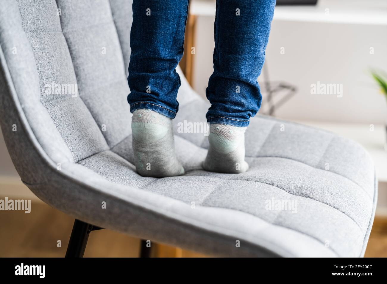 Child Girl Climbing Furniture. Accident Safety In Room Stock Photo
