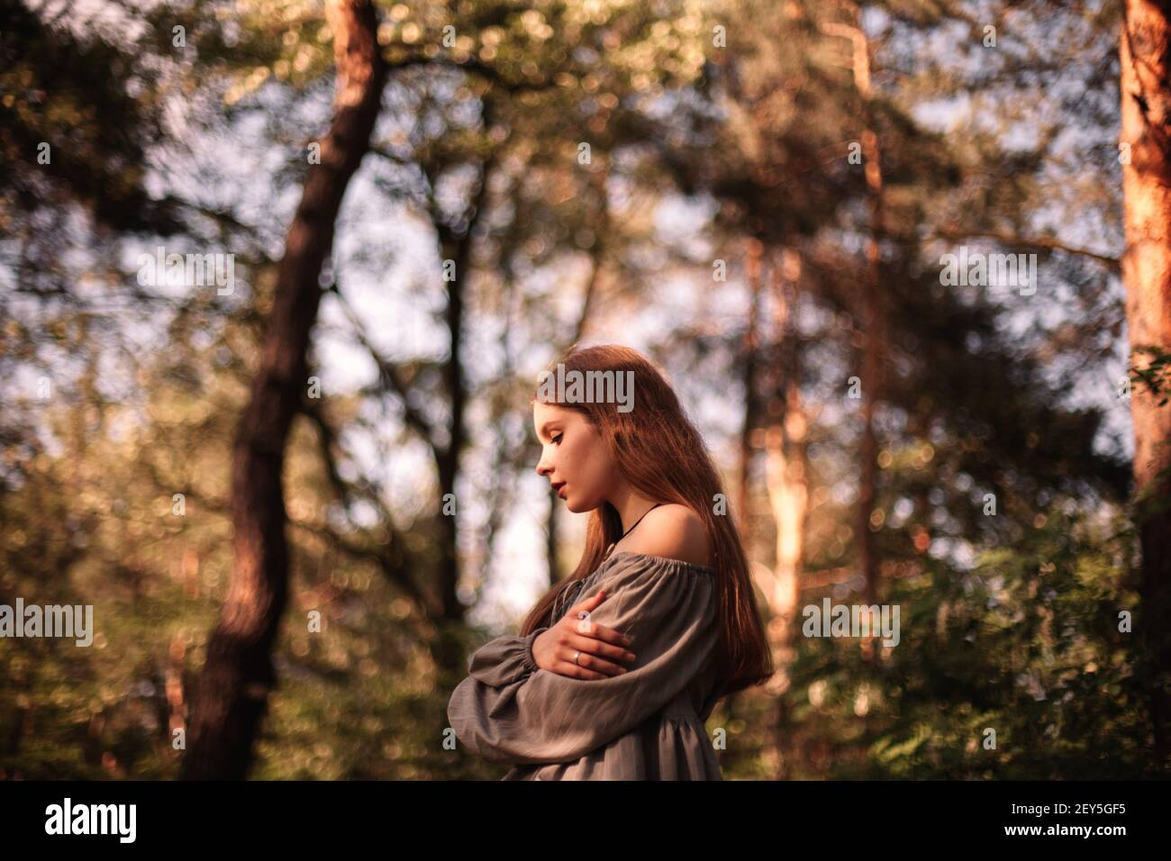 Side view of thoughtful teenage girl standing in forest during summer Stock Photo