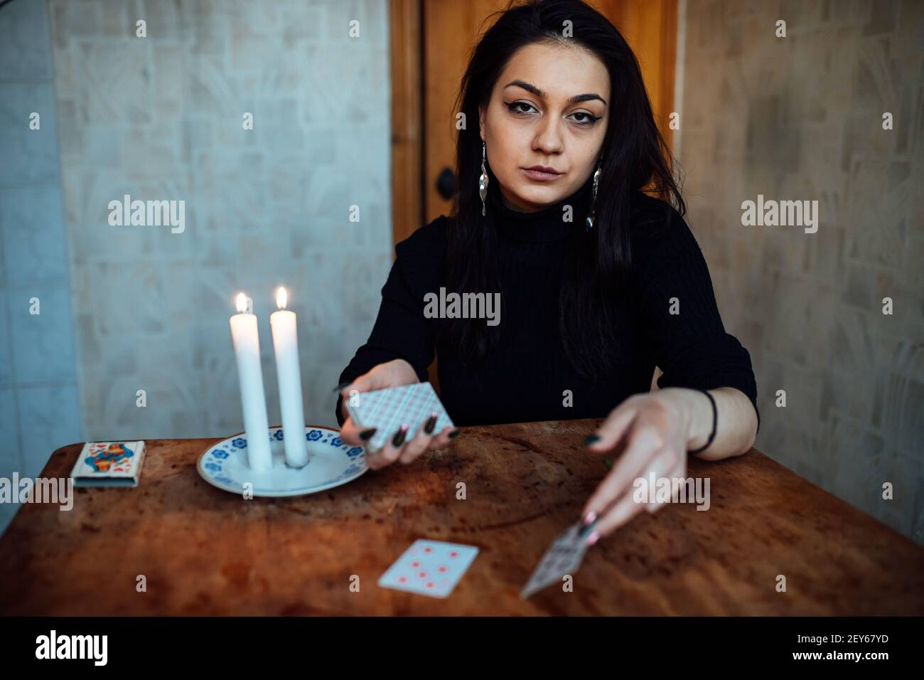 choose a card from the hands of a fortune teller. a woman tells fortunes during a magical ritual. belief in mysticism Stock Photo