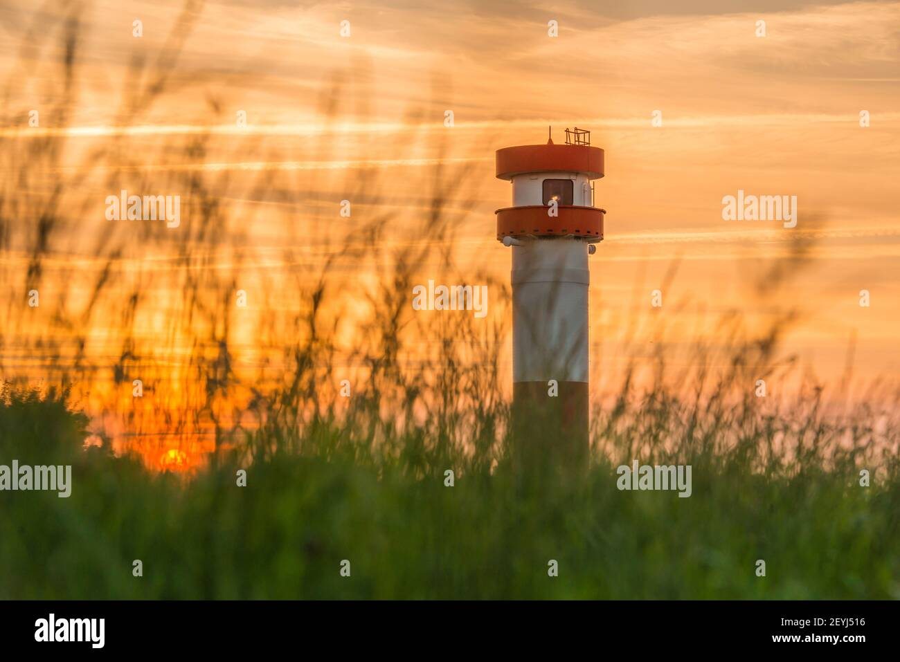Germany, Lower Saxony, Krautsand: Evening mood. The red-white lighthouse and sunset on the Krautsand Elbinsel. Stock Photo