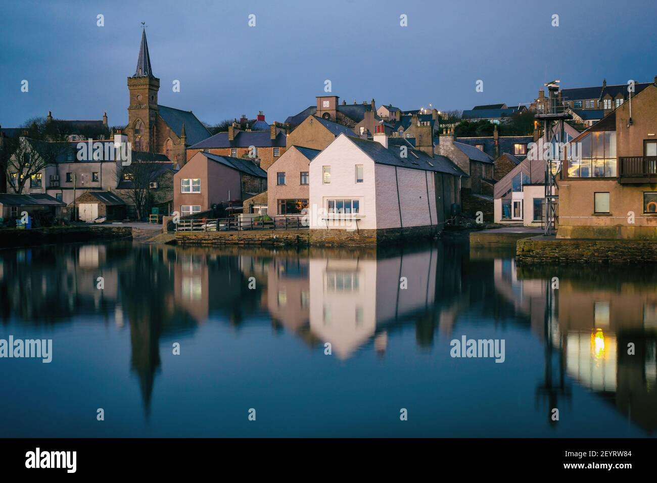 View from water side of scottish houses on Orkney islands with buildings reflections in water in the morning Stock Photo