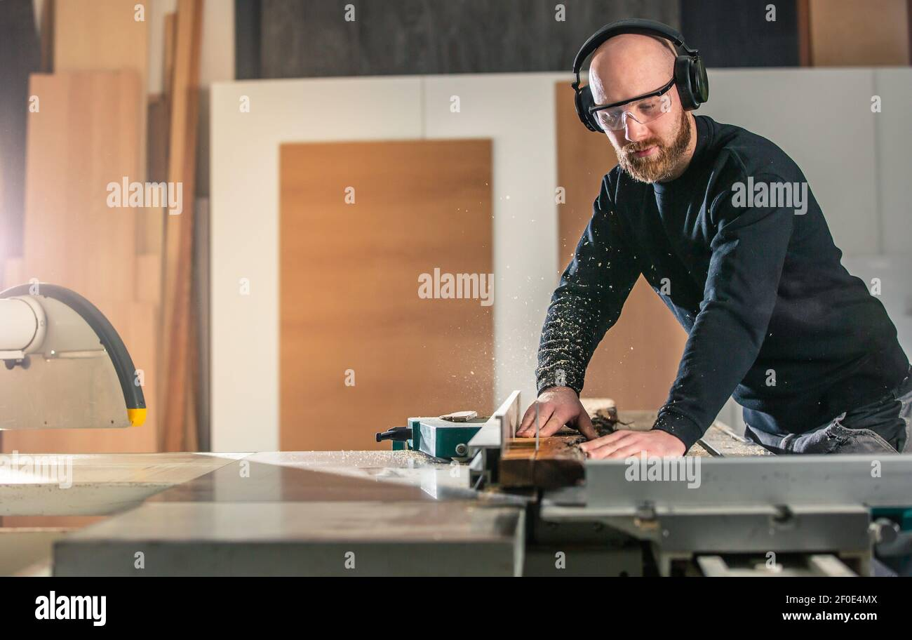 Joinery, woodworking and furniture making, professional carpenter cutting wood in the carpentry shop, industrial concept Stock Photo