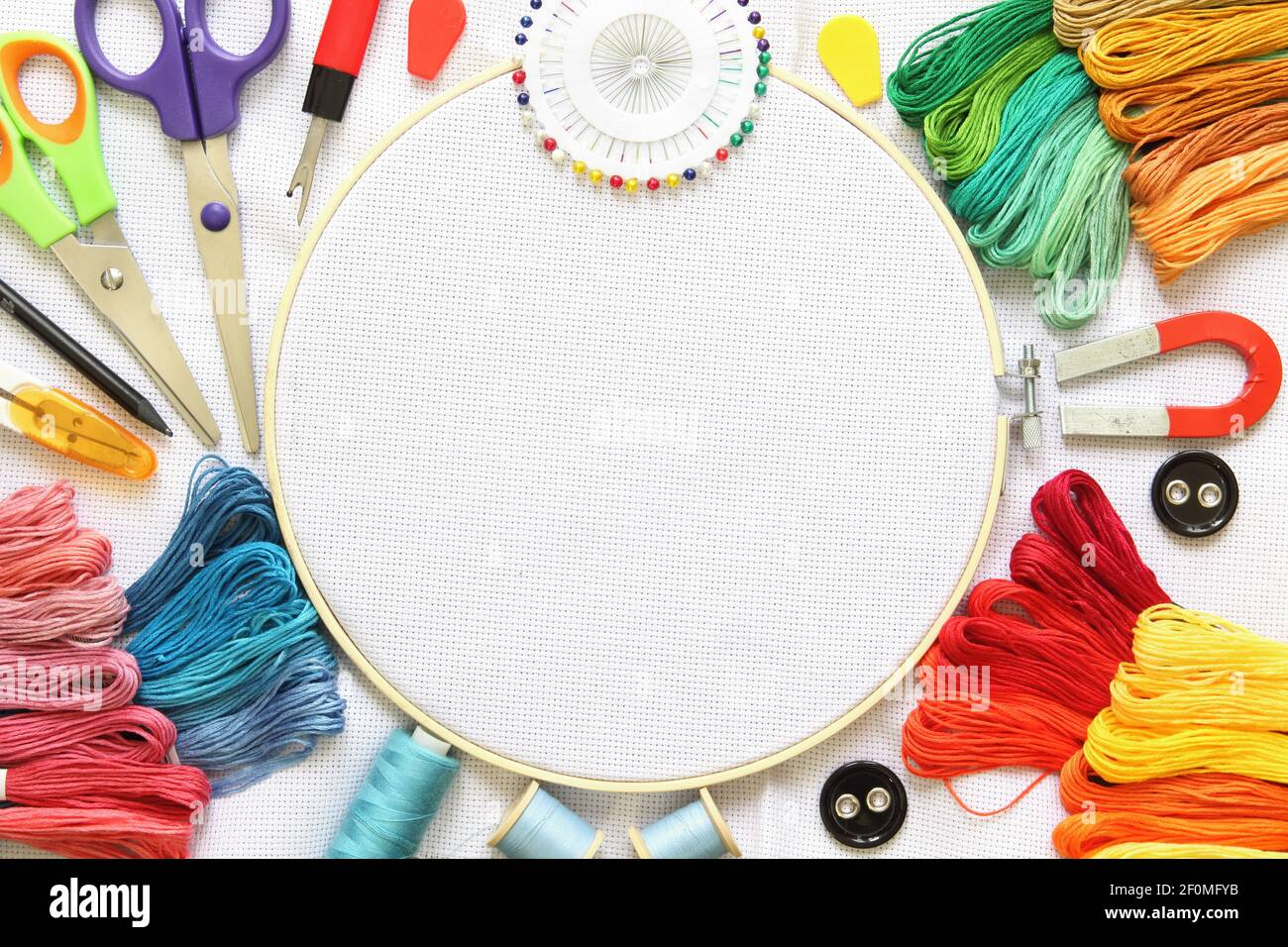 Embroidery hoop and multicolored accessories on white linen canvas with spools of thread, needle and scissors. Stock Photo