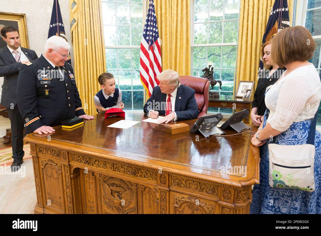 President Donald Trump writes a note of excuse from school note for Medal of Honor recipient retired U.S. Army Capt. Gary M. Rose grandson Christian left during a family visit in the Oval Room at the White House in Washington D.C.   October 23 2017 Stock Photo