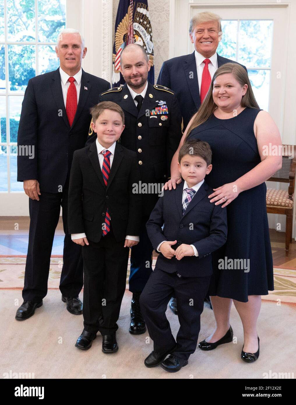 President Donald Trump and Vice President Mike Pence pose for a photo with Medal of Honor recipient retired U.S. Army Staff Sgt. Ronald J. Shurer II his wife Miranda and sons Monday Oct. 1 2018 in the Oval Office Stock Photo