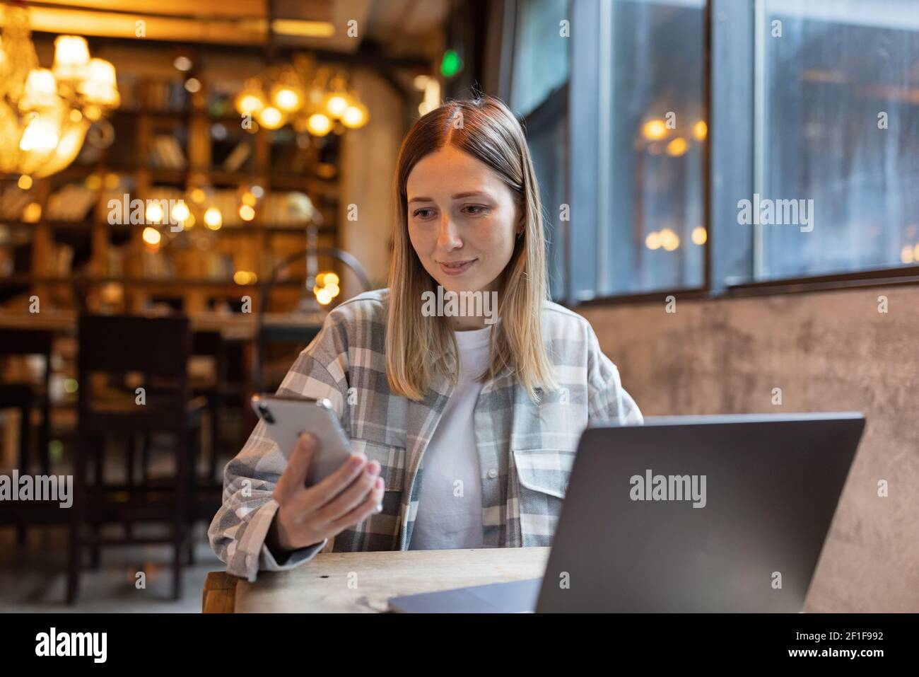 Young Caucasian business woman with blonde hair working on laptop in cafe. College student using technology , online education, freelance  Stock Photo