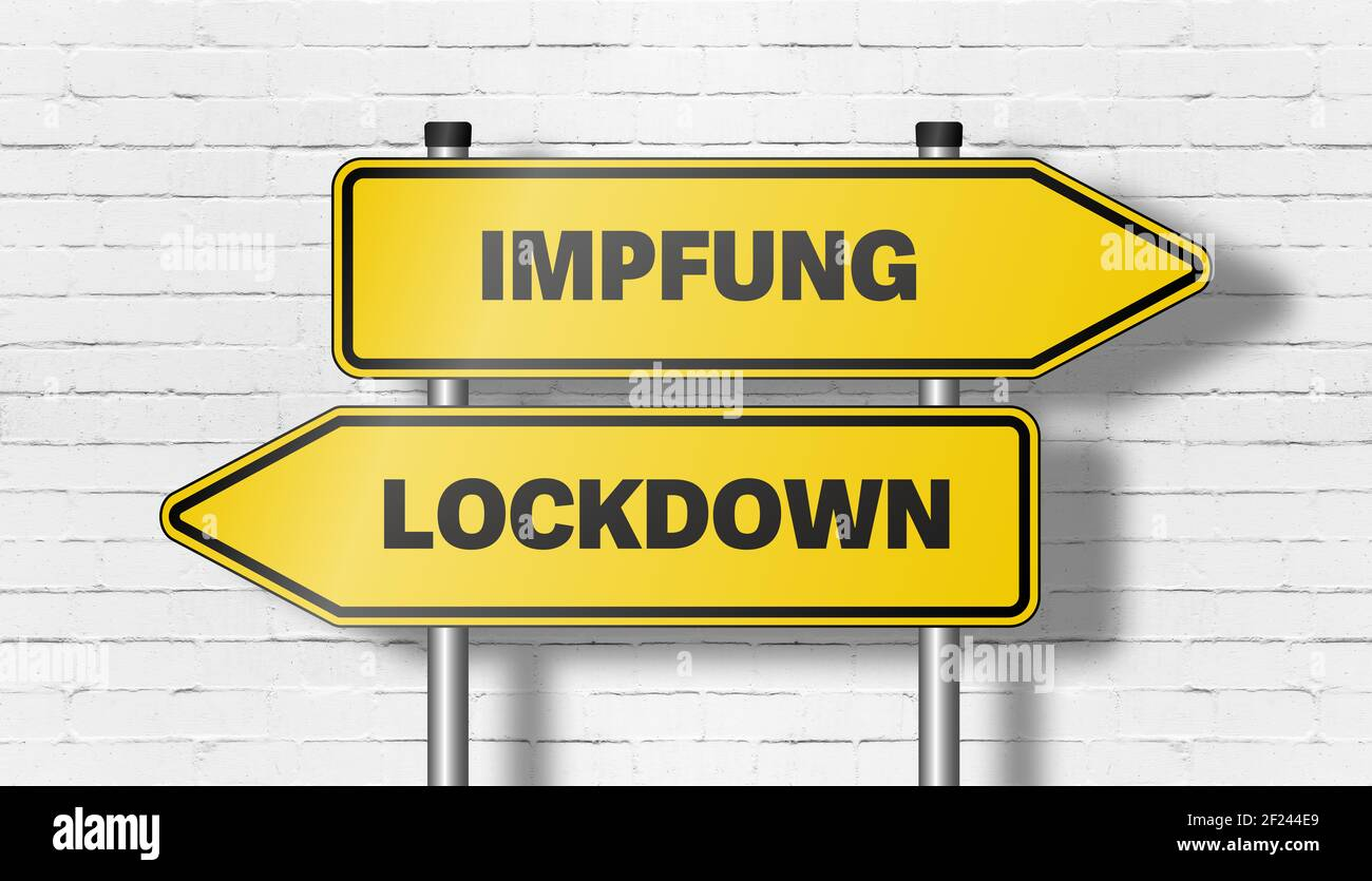 signpost with directional road signs pointing in both directions with words IMPFUNG, German for vaccination, and LOCKDOWN against wall Stock Photo