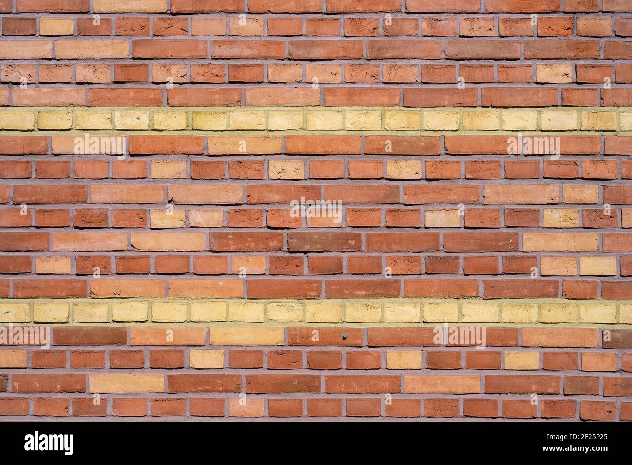 Background from a red brick wall with yellow stripes Stock Photo