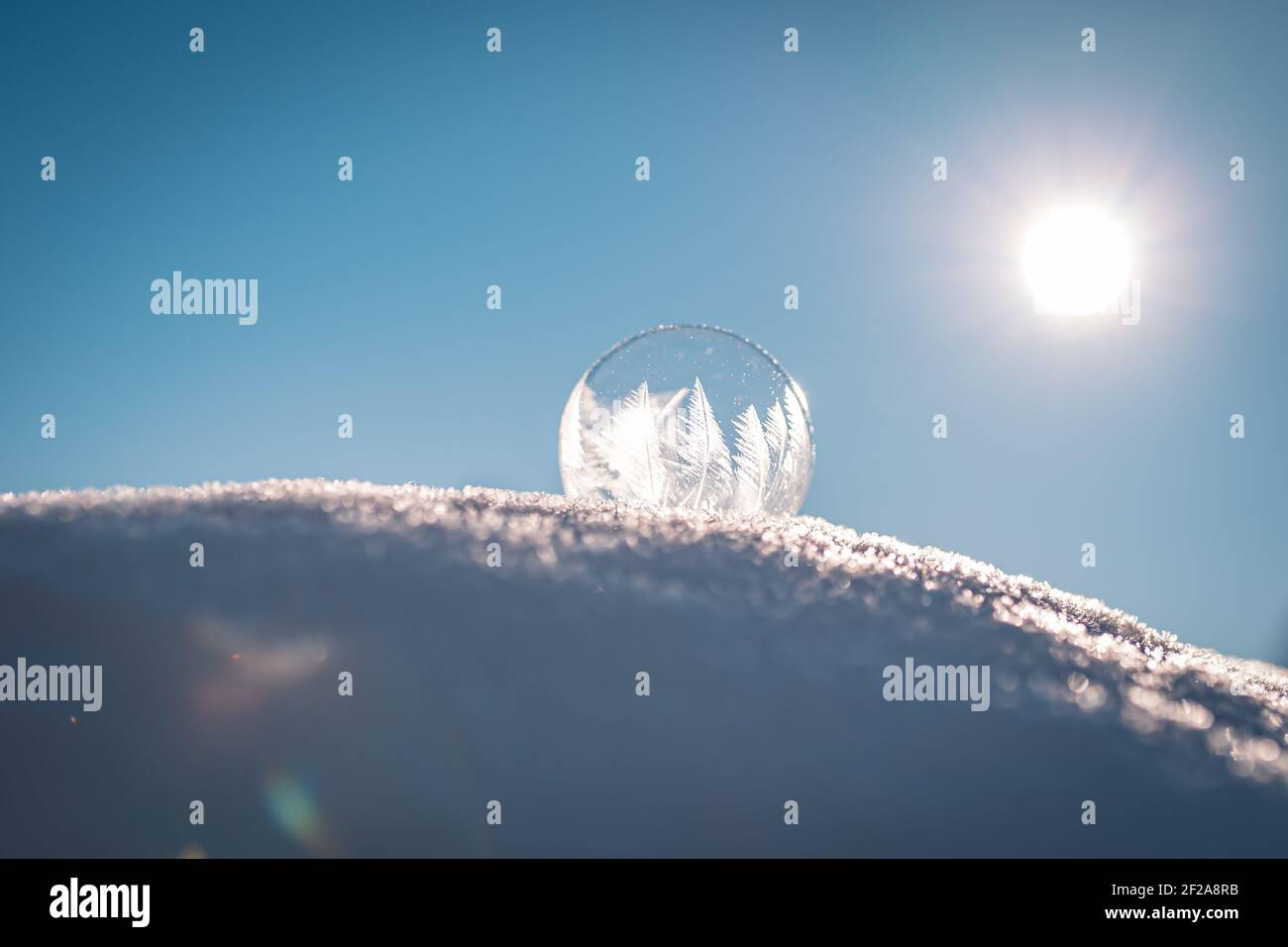 Frozen soap bubble with a beautiful pattern on the snow close up on a blurry background Stock Photo