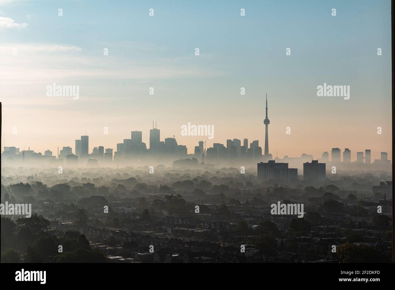 Skyline of Toronto with its CN Tower, seen from a skyscraper in the district The Junction on a foggy autumn morning during sunrise Stock Photo