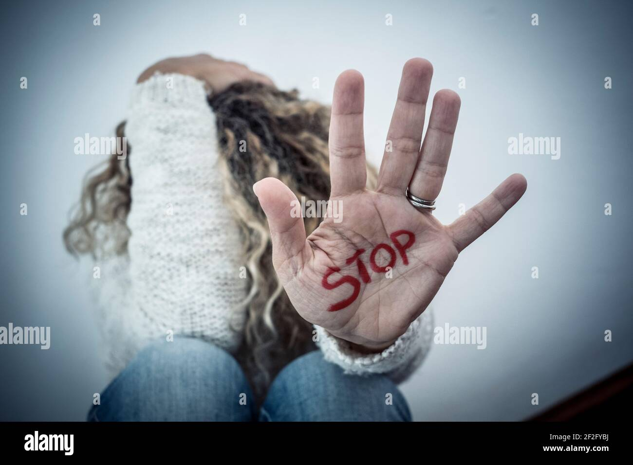 Stop crime violence abuse on women from men - woman protect herself sitting on the ground with hand to defense - home crime violence and couple abuese Stock Photo