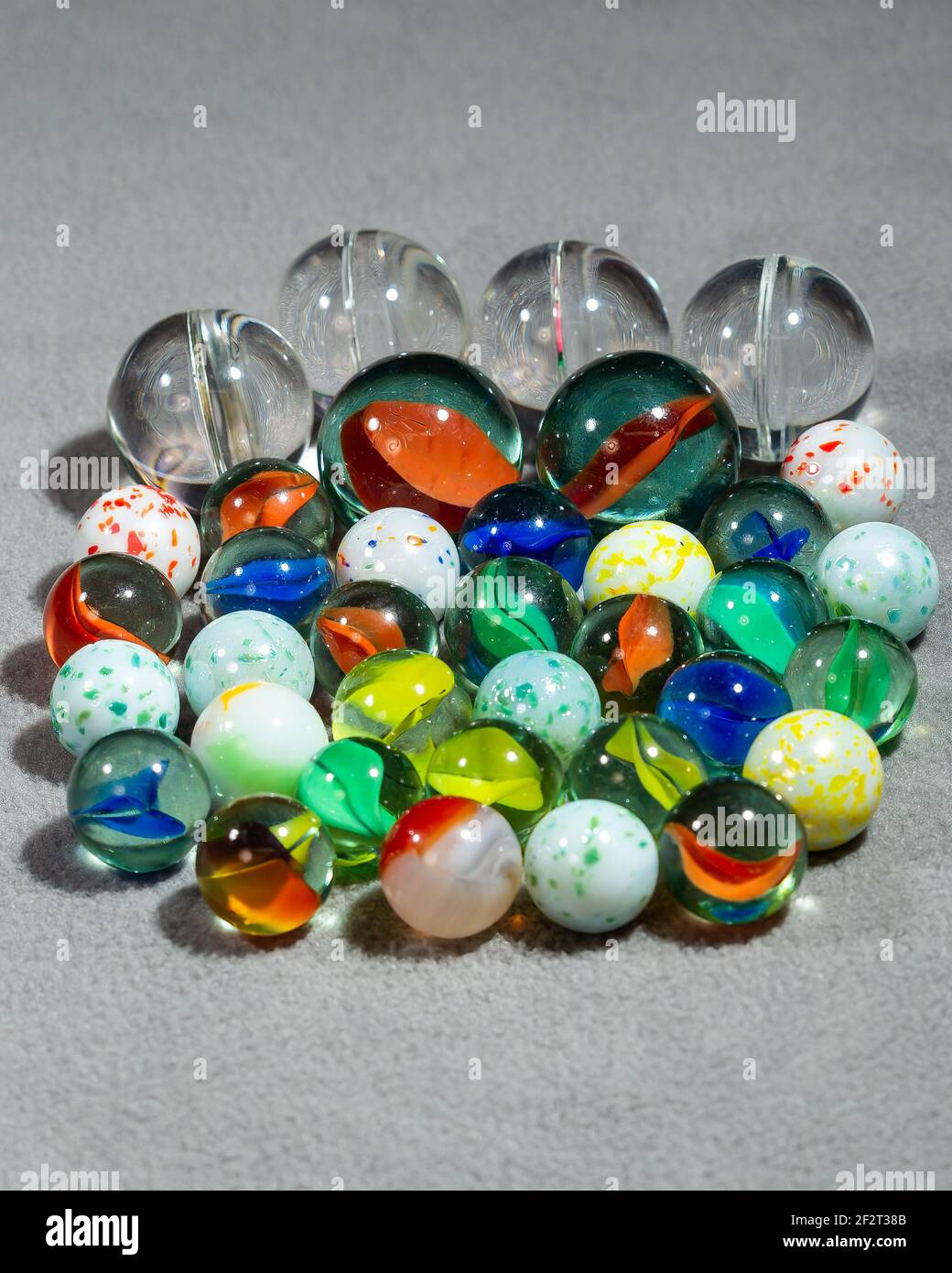 collection of various types and sizes of marbles grouped together Stock Photo