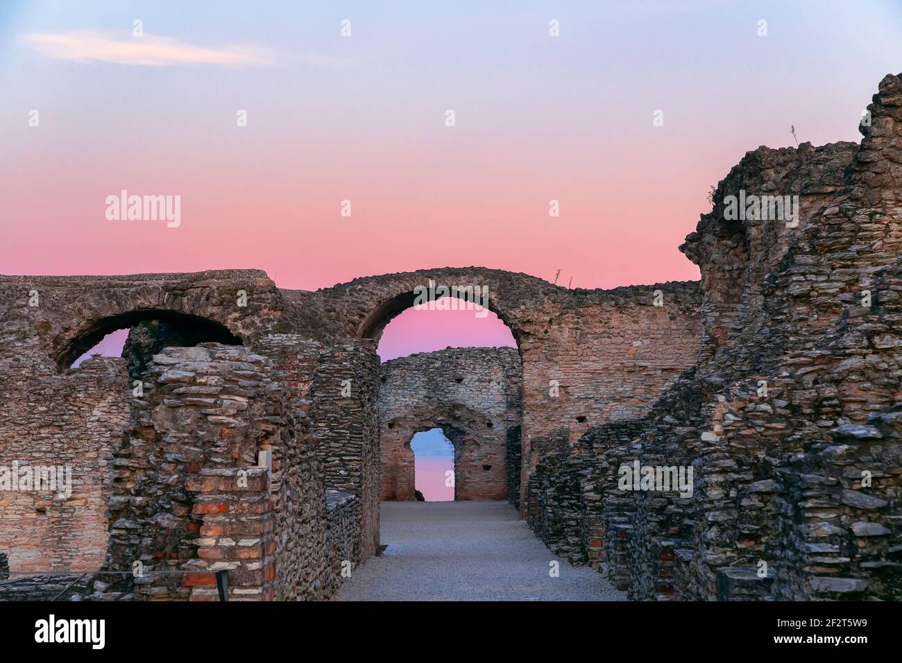 Scenic ruins in the rays of sunset of Grottoes of Catullus, roman villa in Sirmione city, Lake Garda, Italy. Winter time. Stock Photo