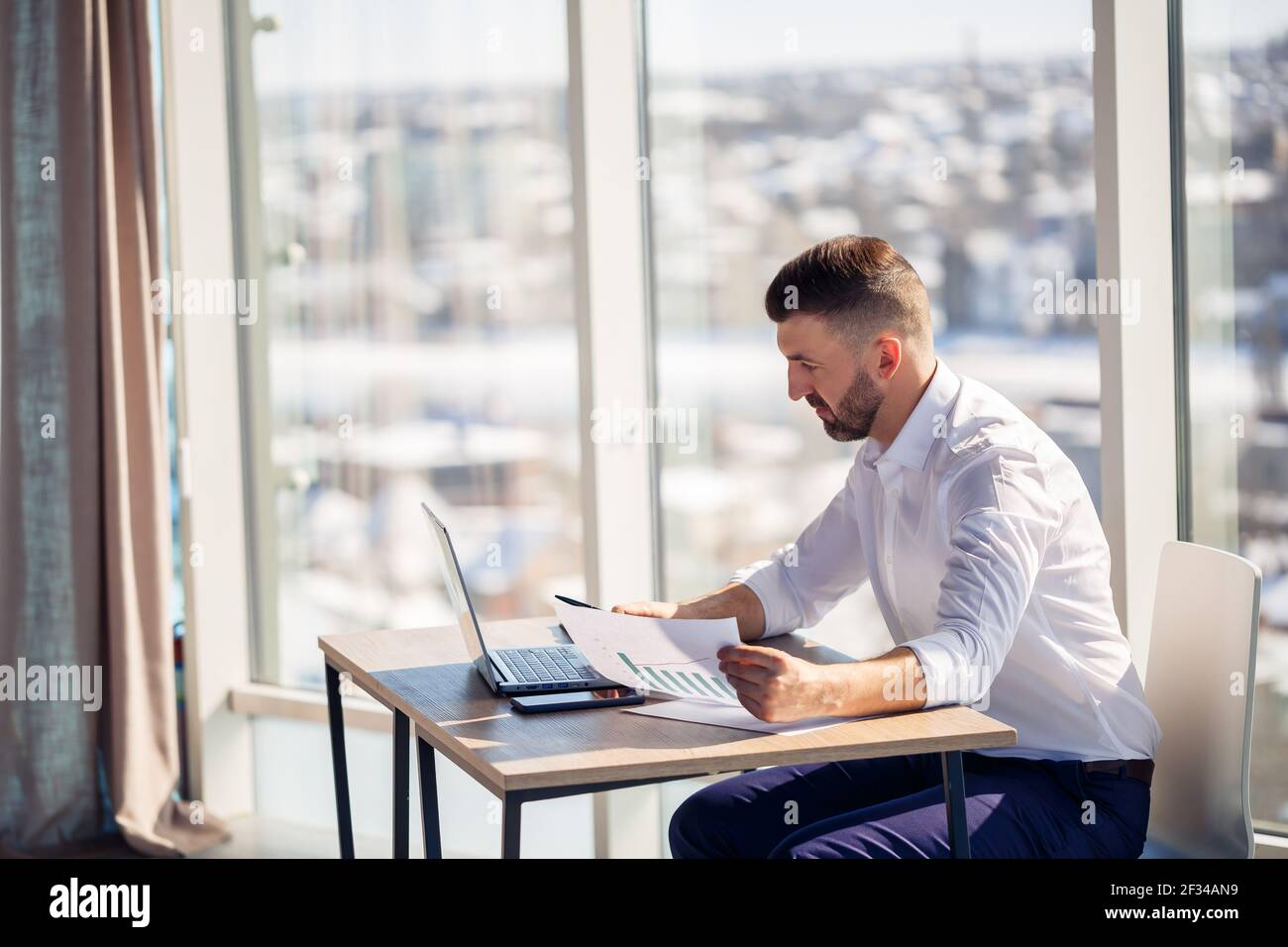 An adult successful male businessman sits in his office with large windows and works at a laptop, working on new projects. Stock Photo