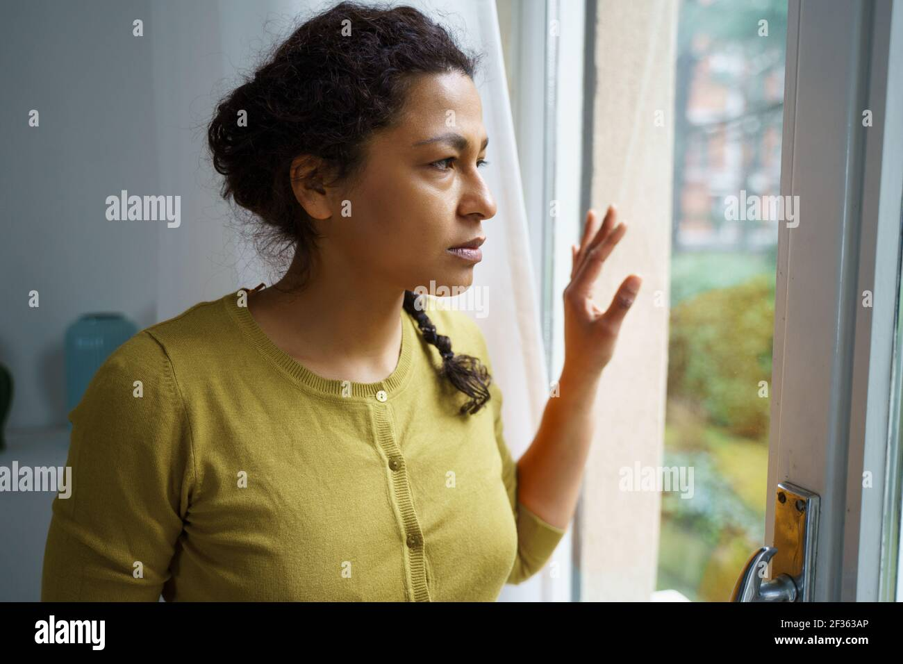Worried black woman looking out of the window Stock Photo