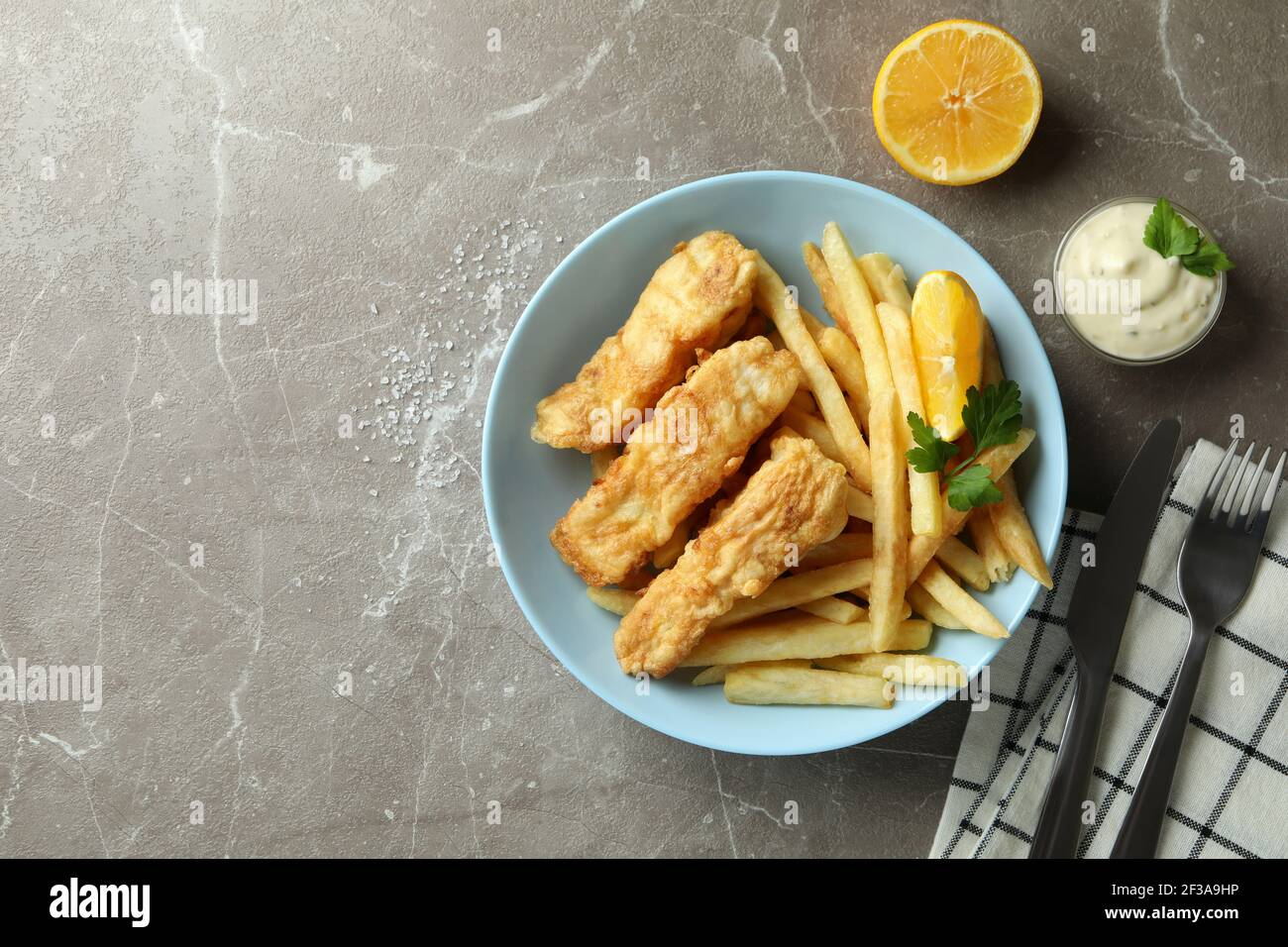 Concept of tasty eating with fried fish and chips on gray textured table Stock Photo
