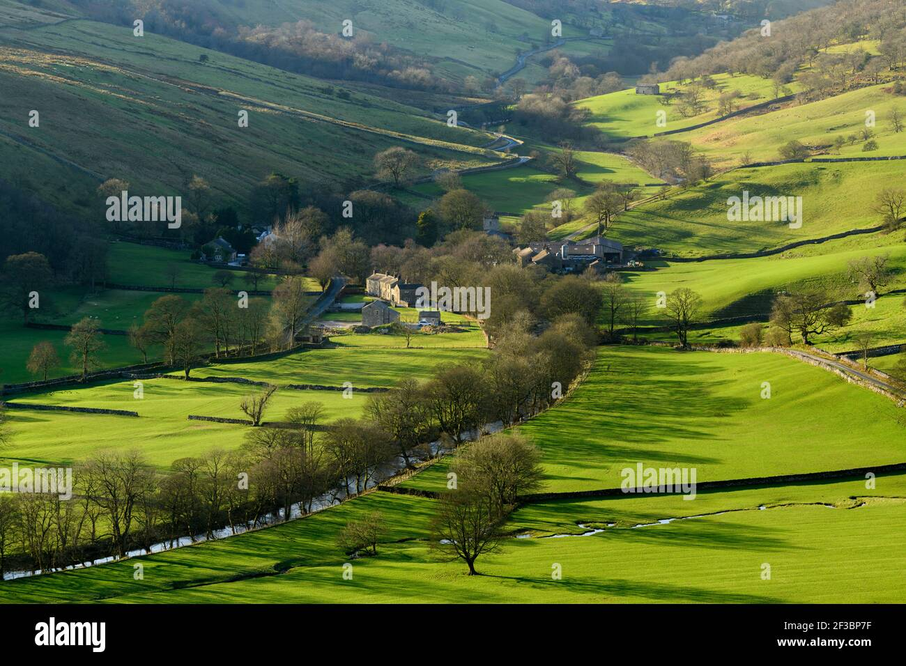 Picturesque Dales village (cottages & farms) & River Wharfe, nestling by hills & hillsides in steep-sided valley - Hubberholme, Yorkshire, England, UK Stock Photo