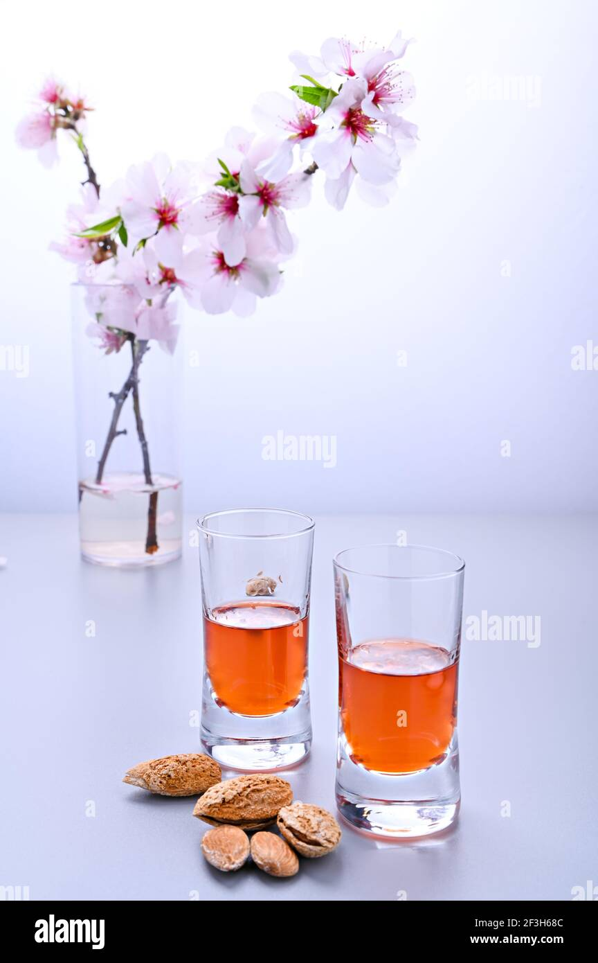 almond liquor. The traditional strong drink in italy to complete the dinner is a liqueur made from nuts and berries. Ratafia, alcohol in shot. on the table and a branch of blooming almonds. Copy space Stock Photo