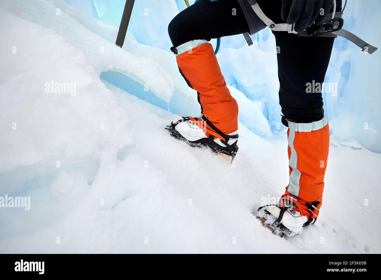Woman climber in orange gaiters with ice axe near frozen waterfall in the mountains in Almaty, Kazakhstan Stock Photo