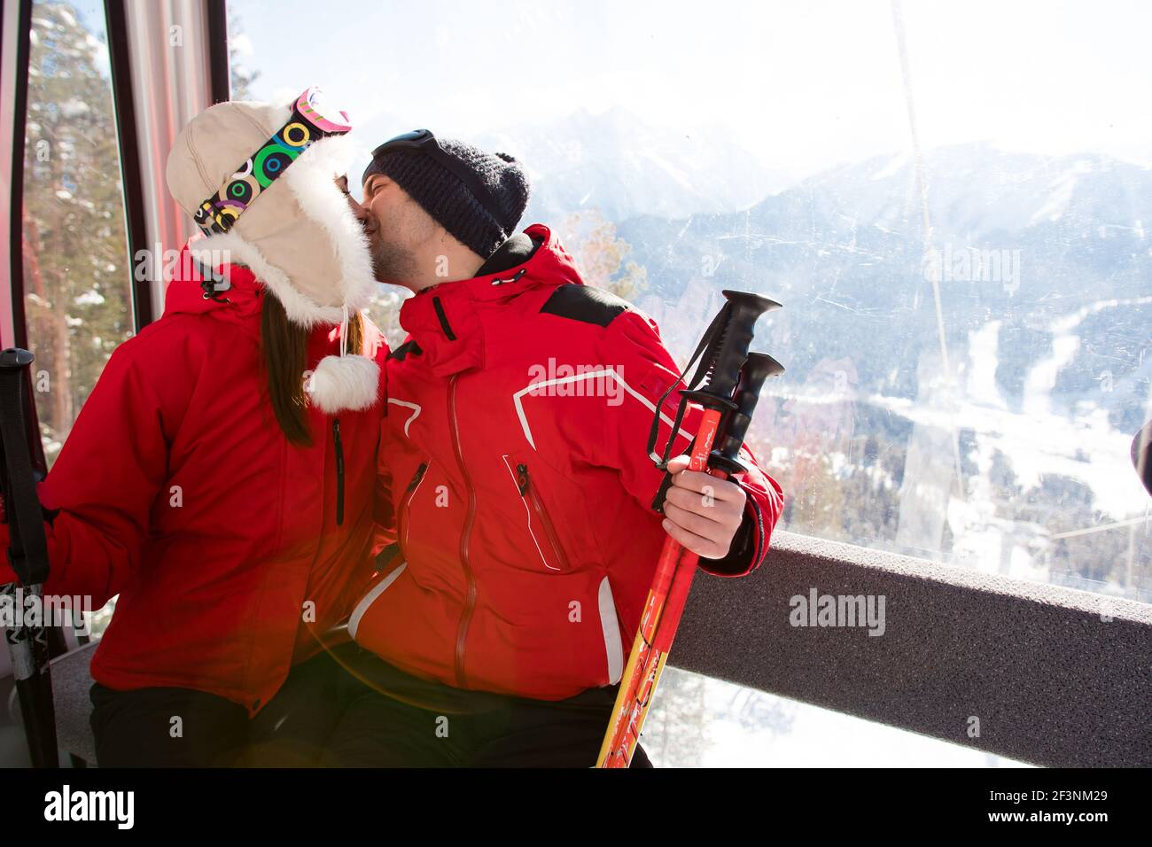 cheerful friends on ski lift ride up on snowy mountain Stock Photo