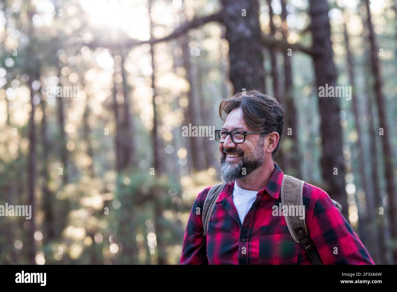 Close up portrait of confident bearded man in a outdoor park. Profile young handsome smiling bearded man Young adult hipster hiking forest - happy peo Stock Photo