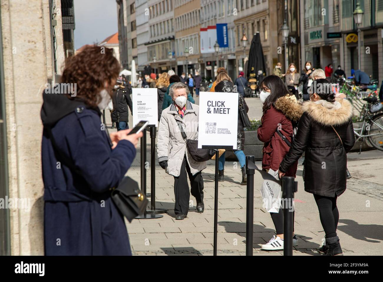 Junge Frau vereinbart Click & Meet Termin, um in ein Geschäft zu kommen. Während die Inzidenz in München weiter ansteigt und evtl. bald die Geschäfte wieder schließen müssen, sind viele Menschen am 18. März 2021 in der Münchner Innenstadt unterwegs und kaufen ein. Die neuen Varianten des Coronavirus betragen in der Landeshauptstadt aktuell fast 70%. * While the incidence is rising and the shops may have to close again, many people on March 18 2021 go to the pedestrian zone in Munich, Germany and buy stuff. The number of new variants in Munich is about 70%. (Photo by Alexander Pohl/Sipa USA Stock Photo