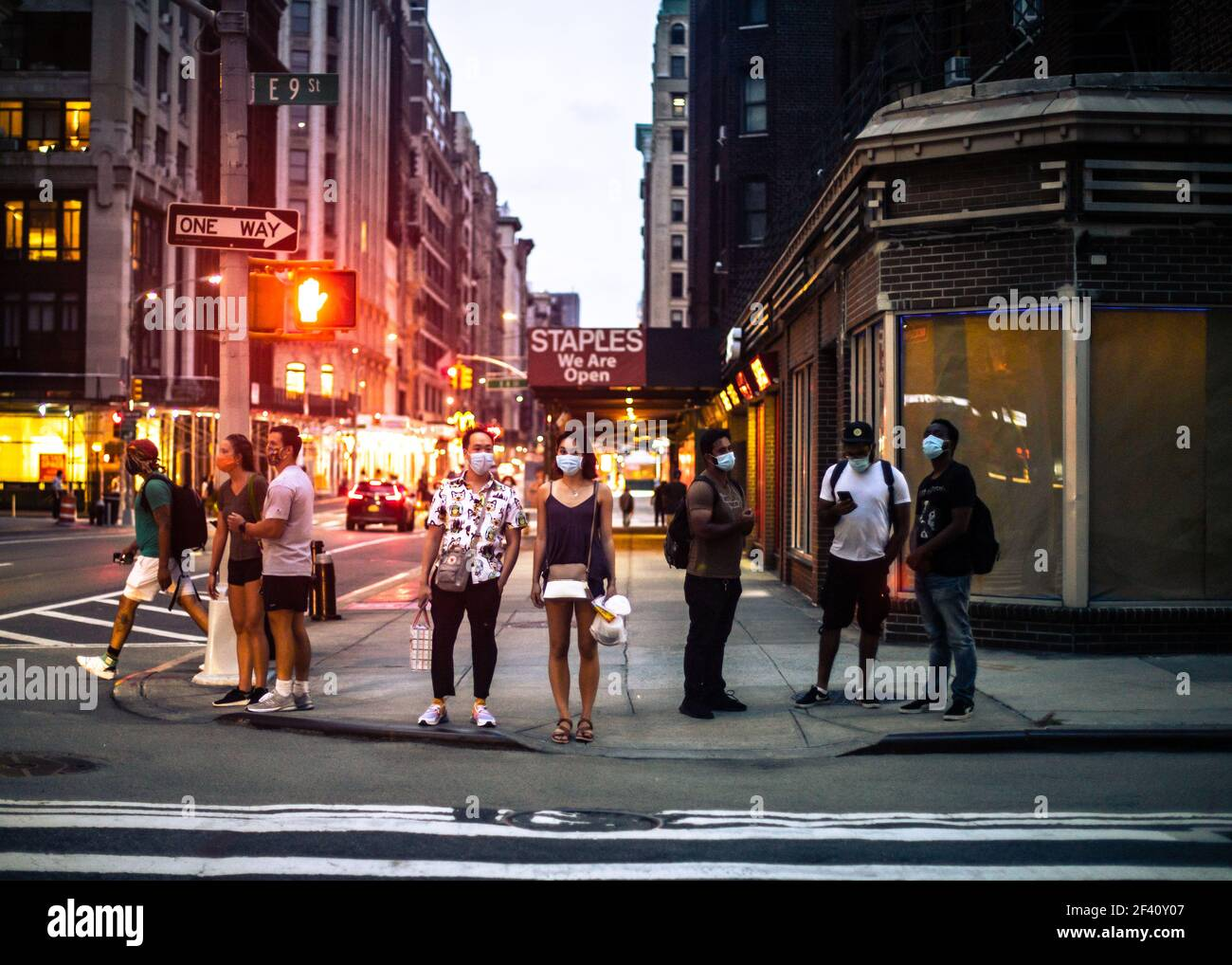 New York City, New York - August 18, 2020:  Street scene from Manhattan on a summer evening of people waiting to cross the street wearing masks during Stock Photo